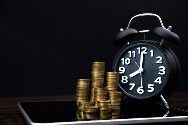 Coins stacks and alarm clock with tablet computer and financial graph, business planning vision and finance analysis concept Premium Photo