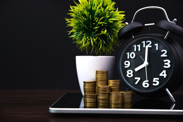 Coins stacks and alarm clock with tablet computer and financial graph Premium Photo