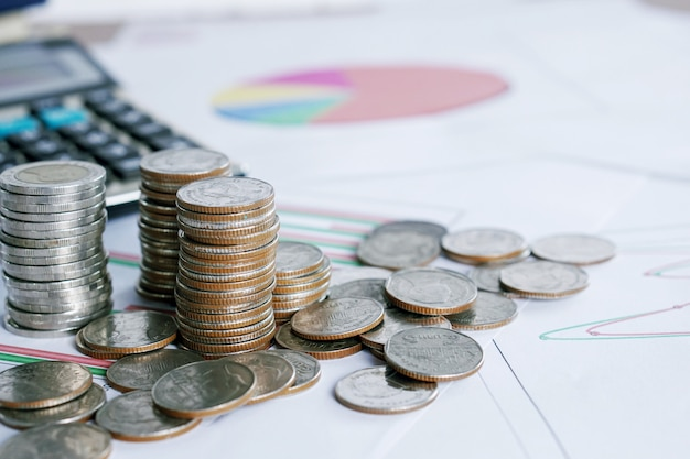 Coins on with calculator on financial graph Premium Photo