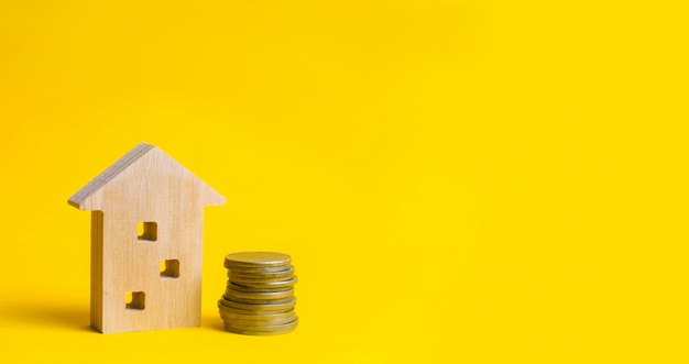 Coins and wooden house on a yellow background Premium Photo