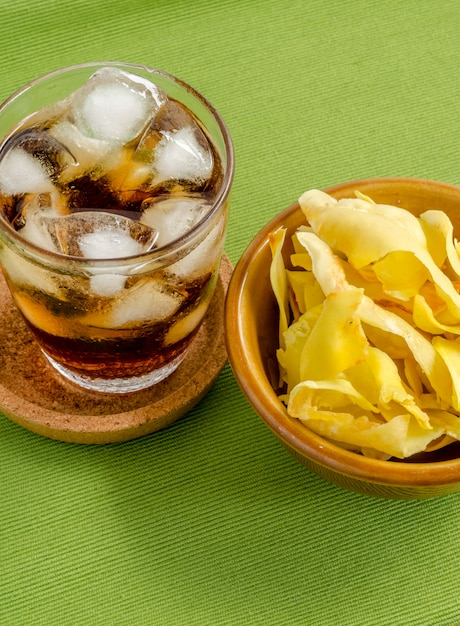 Cola and durian chips fried snack fruit in brown blow on green background Premium Photo