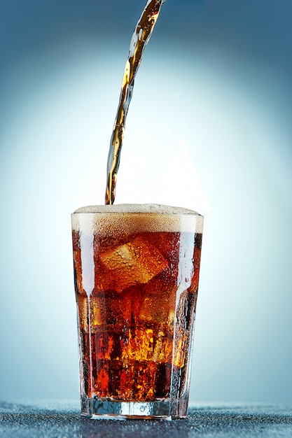 Cola pouring in a glass Free Photo