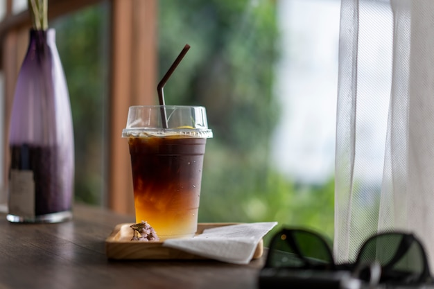 Cold black coffee drinks placed on a wooden table Premium Photo