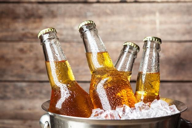Холодные бутылки пива в ведре Premium Фотографии