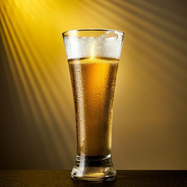暗いテーブルの上に滴を入れたグラスに冷たいクラフトライトビール。黄色の背景にビールのパイント。 Premium写真