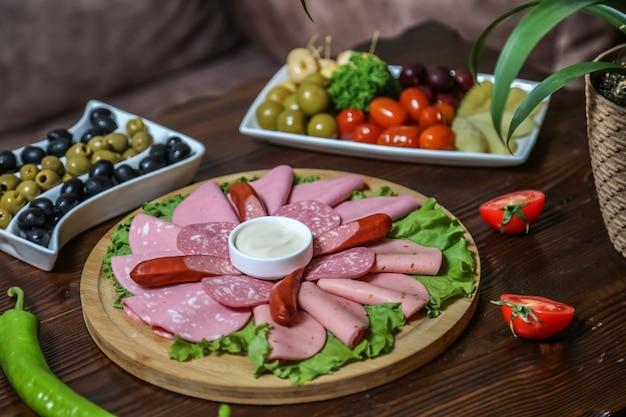 Колбасы и соленые колбаски ветчина оливки помидор огурец вид сбоку Бесплатные Фотографии