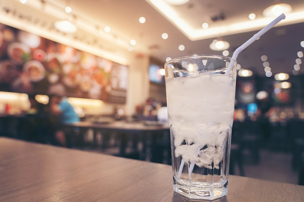 Cold glass of ice water on wooden table and light blurred in restaurant background Premium Photo