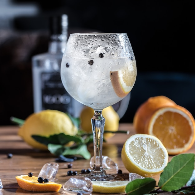 A cold lemon cocktail with ice slices is on the table with whole lemons and oranges Premium Photo