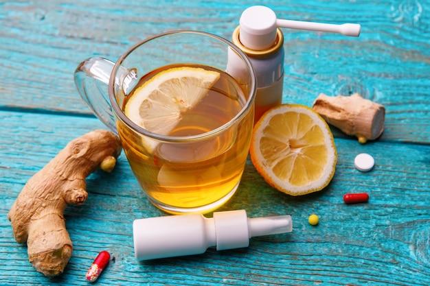 Лекарства от простуды, чай, лимон и имбирь на деревянном синем Premium Фотографии