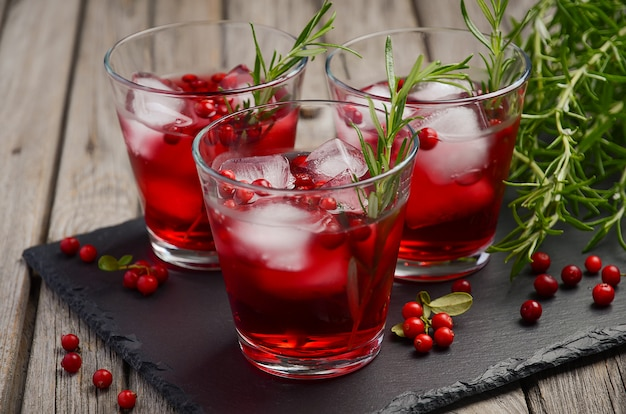 Cold refreshing drink with cranberries and rosemary on a wooden background. Premium Photo