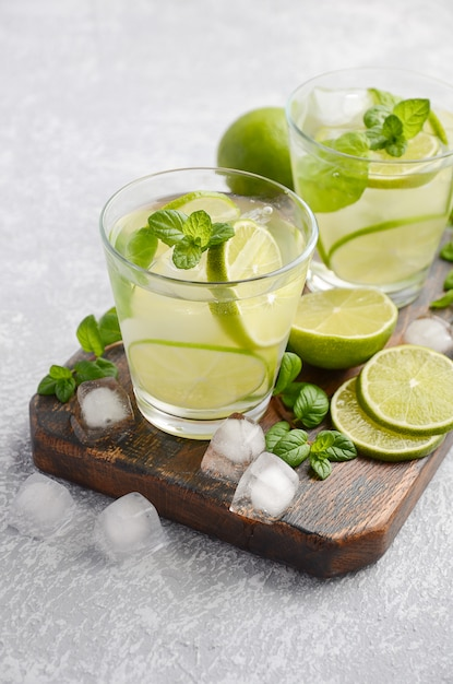Cold refreshing summer drink with lime and mint in a glass on a gray concrete or stone. Premium Photo
