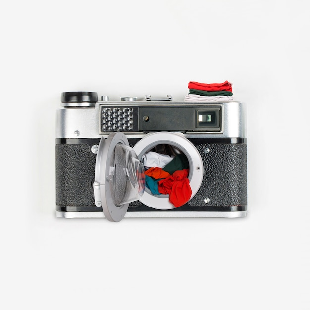 Collage made out of vintage camera and washing machine with clothes Premium Photo