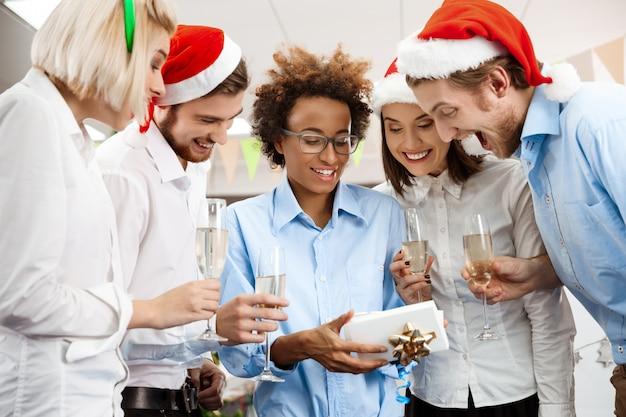 주는 선물을 미소 사무실에서 크리스마스 파티를 축 하하는 동료. 무료 사진