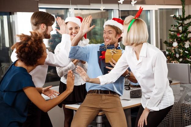 Colleghi che celebrano la festa di natale in ufficio sorridendo dando regali. Foto Gratuite