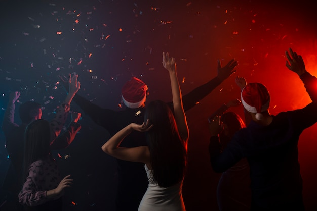 Colleagues dancing in confetti at new years party Free Photo