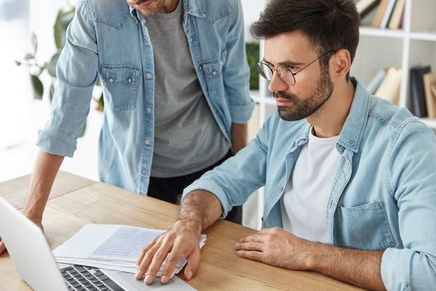 同僚は、ドキュメントに囲まれたラップトップコンピュータに焦点を当て、利益を上げるための新しいアイデアについて話し合います 無料写真