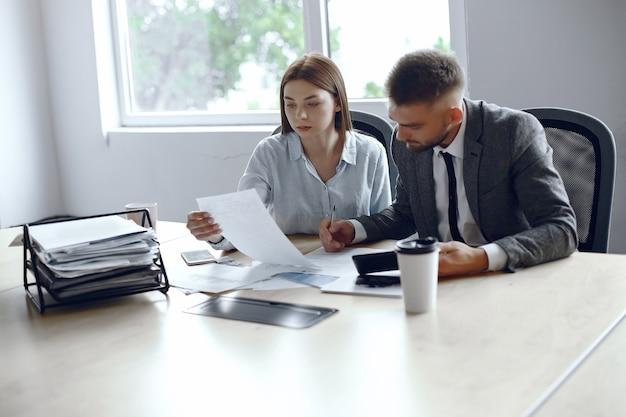I colleghi bevono caffè partner d'affari in una riunione d'affari uomo e donna seduti al tavolo Foto Gratuite