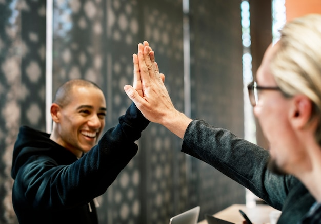 Colleagues giving a high five Free Photo