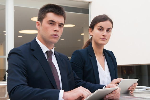 Colleagues looking at camera and holding tablets at desk Free Photo