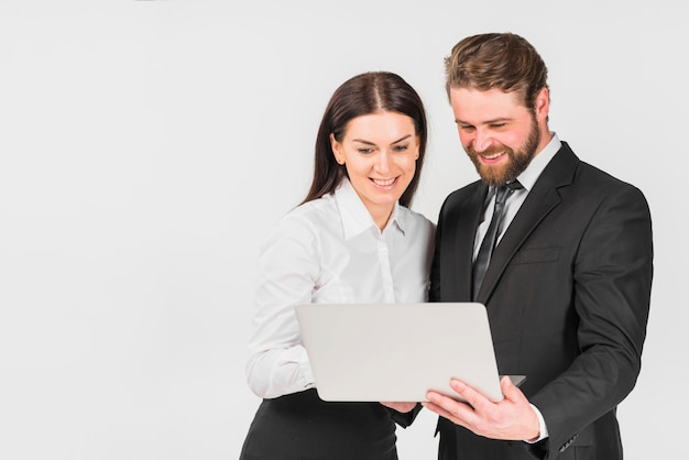 Colleagues male and female smiling and looking at laptop Free Photo