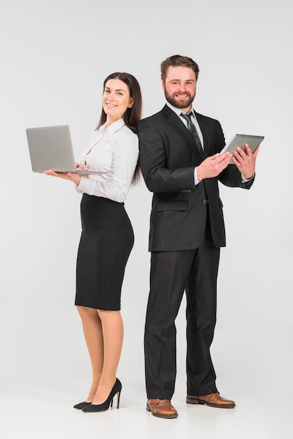 Colleagues male and female standing with gadgets and smiling Free Photo