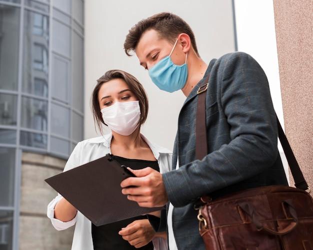 Коллеги на открытом воздухе во время пандемии, глядя в блокнот с масками для лица Бесплатные Фотографии