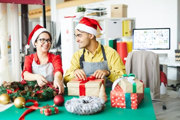 Colleghi che preparano decorazioni natalizie e confezionano regali Foto Gratuite
