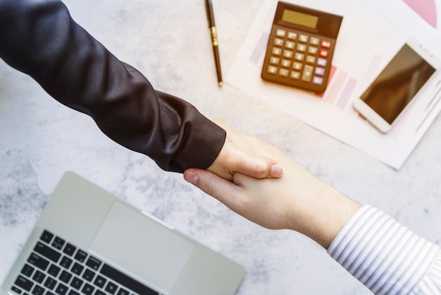 Colleagues shaking hands above desk Free Photo