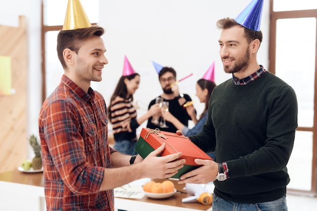 Colleagues surprise another employee of company. Premium Photo