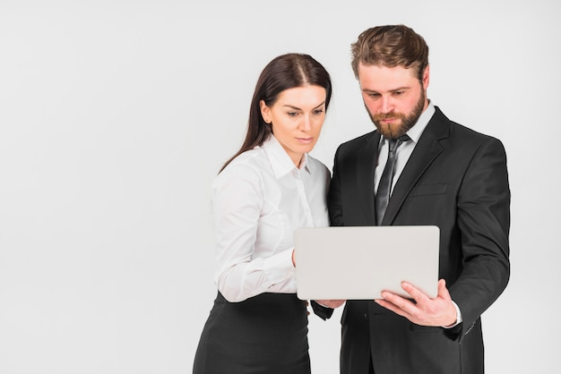 Colleagues woman and man looking at laptop Free Photo