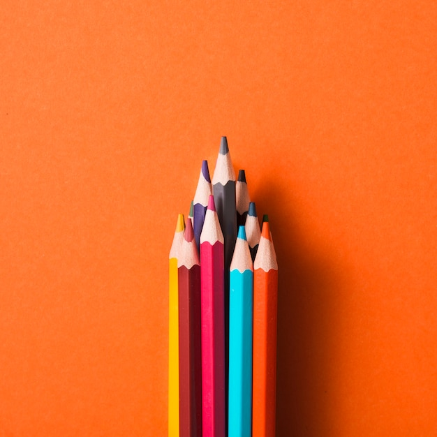 Collection of colored pencils on an orange background Free Photo
