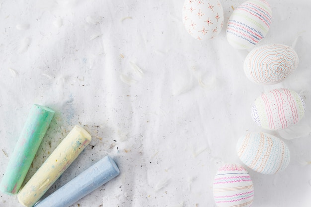 Collection of easter eggs with patterns near quills and chalks on textile Free Photo