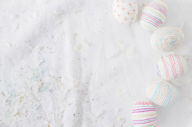 Collection of easter eggs with patterns near quills on textile Free Photo