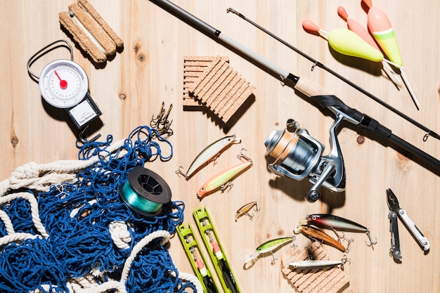 Collection of fishing equipment on wooden surface Free Photo