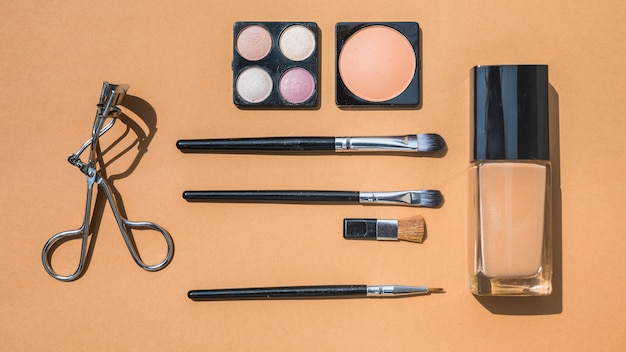Collection of make up and cosmetic beauty products arranged on ochre background Free Photo