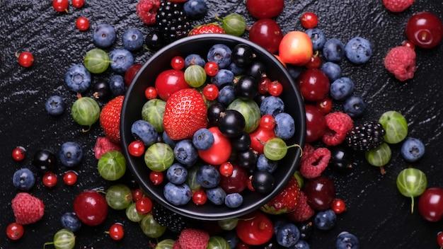 Сбор свежих лесных ягод на черном деревянном, вид сверху Бесплатные Фотографии
