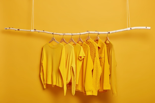 탈의실에서 선반에 매달려있는 여성을위한 일반 노란색 스웨터와 재킷 컬렉션. 선택적 초점. 유행 겨울이나 가을 옷. 무료 사진