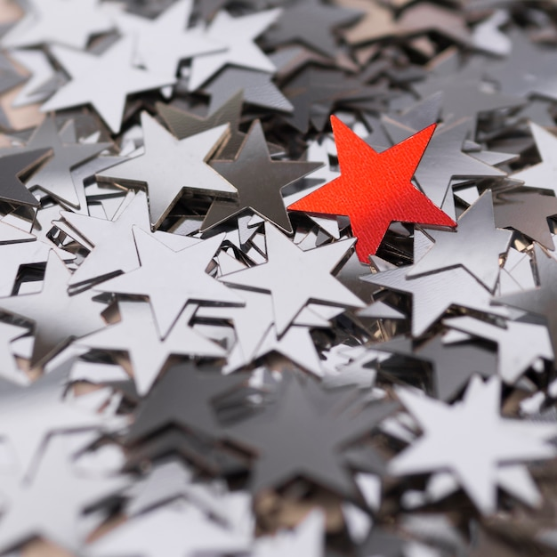 Collection of silver stars surrounding a red one Free Photo