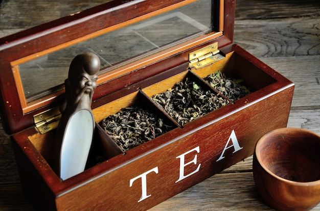 A collection of tea in a wooden box, a wooden glass with a stylized teaspoon on a wooden background. Premium Photo