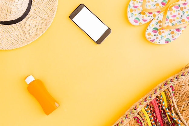 Collection of tropical beach vacation belongings and phone on yellow background Free Photo