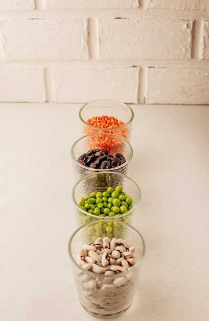 Collection of various dried legumes in glasses Premium Photo
