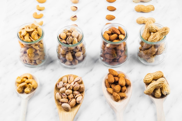 Collection of various nut food in spoon and glass jar on marble surface Free Photo