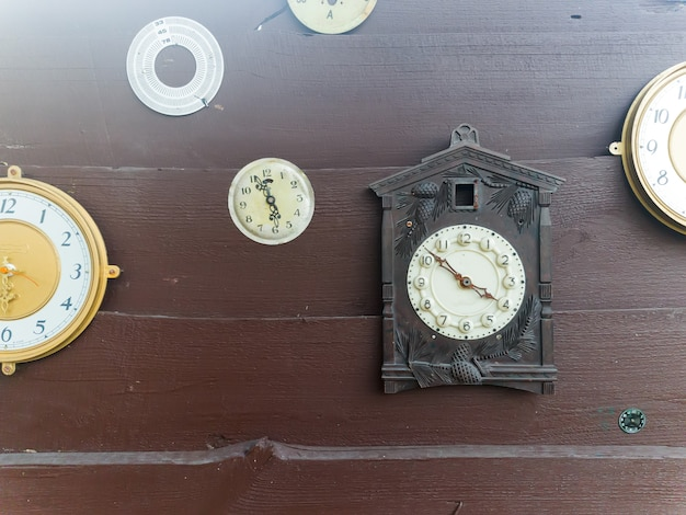 Collection of vintage clock hanging on an old wooden wall on the outdoors with sunshine Premium Photo