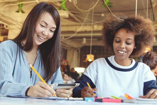 Ragazze del college che fanno compiti a casa alla caffetteria utilizzando tavoletta digitale e prendere appunti su carta. Foto Gratuite