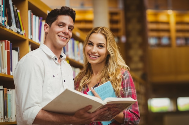 College students reading book together in library Premium Photo