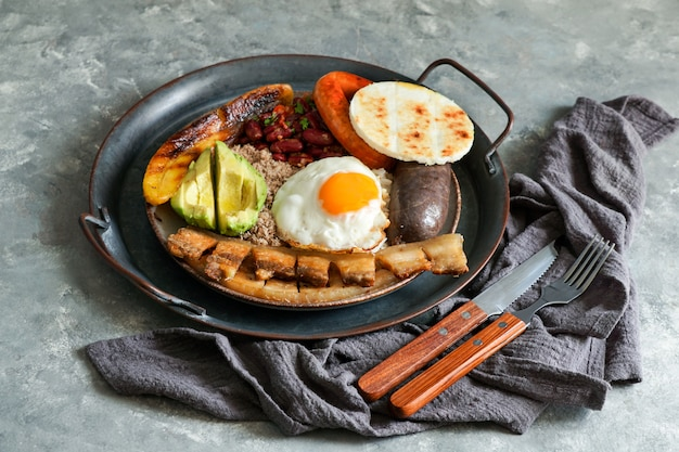 Colombian food. bandeja paisa, typical dish at the antioquia region of colombia - chicharron (fried pork belly), black pudding, sausage, arepa, beans, fried plantain Premium Photo