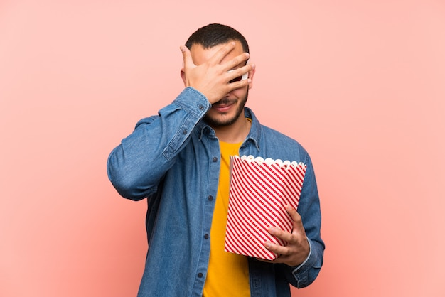 Colombian man with popcorns covering eyes by hands Premium Photo