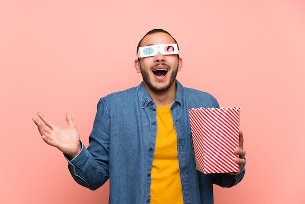 Colombian man with popcorns with surprise and shocked facial expression Premium Photo