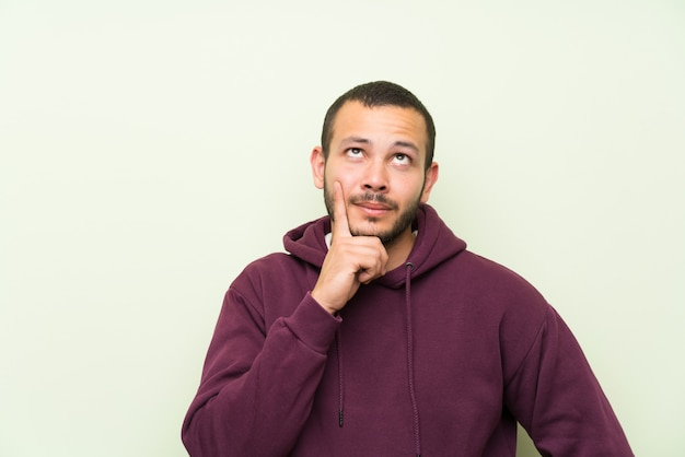 Colombian man with sweatshirt over green wall thinking an idea Premium Photo
