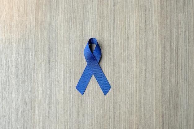 Colon cancer awareness, dark blue ribbon on wooden background Premium Photo